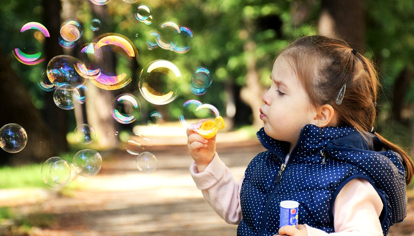Little kid blowing bubbles
