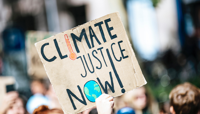 "Sign that says ""Climate Justice Now!"""