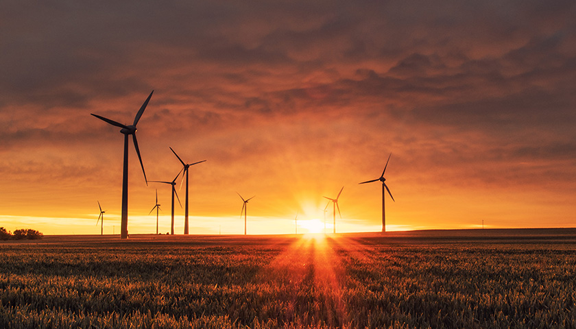 A sunset with a field of windmills
