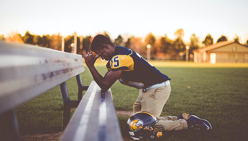 Football player kneeling, praying on bench seat