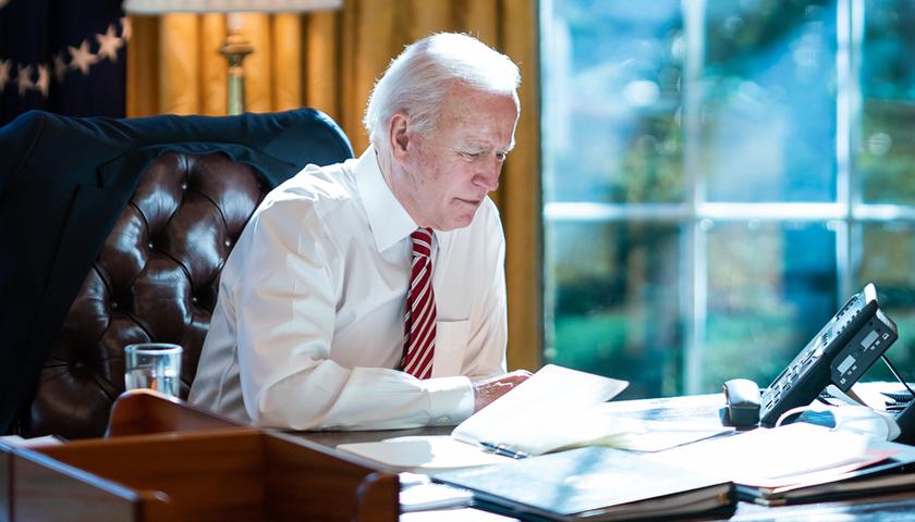Joe Biden at desk, looking over documents