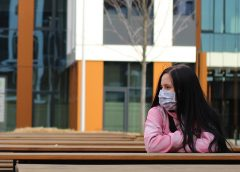Woman sitting alone with a mask on.