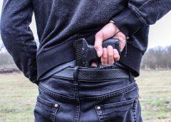 Guy grabbing handgun out of back of pants
