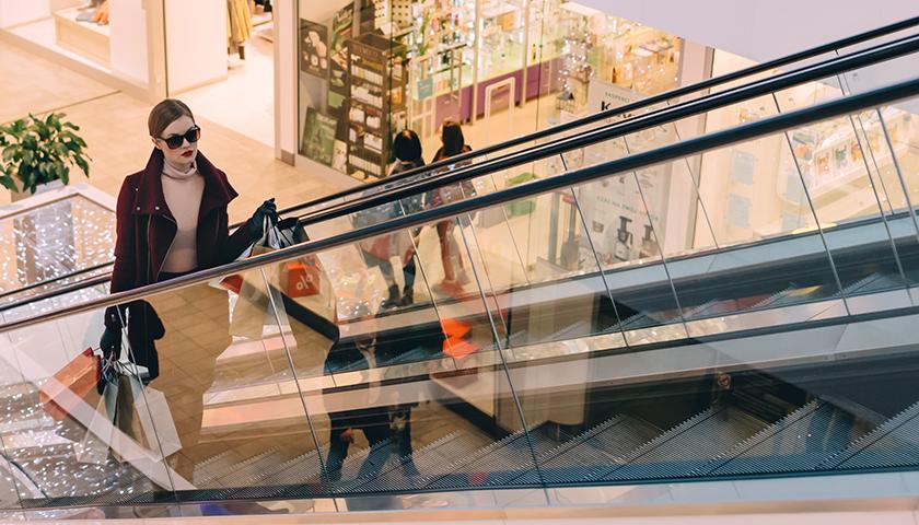 Woman shopping, going up escalator