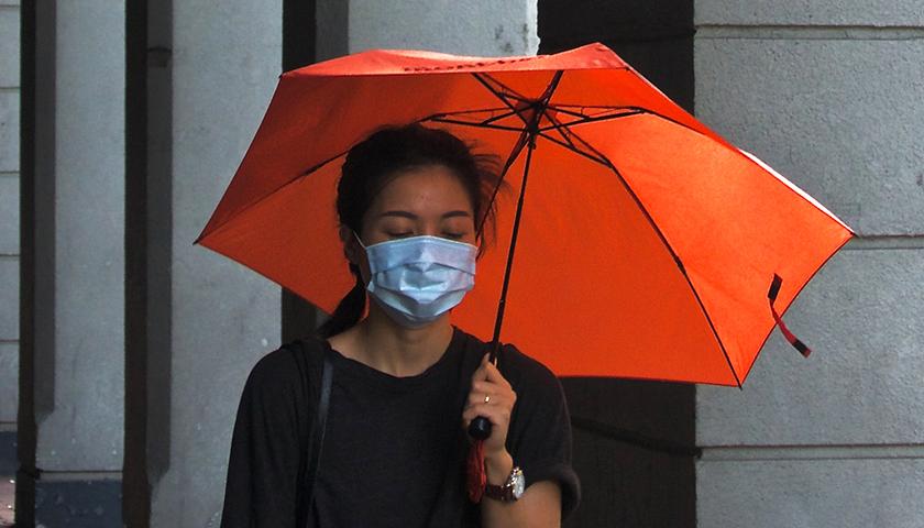 Woman holding orange umbrella, wearing a mask