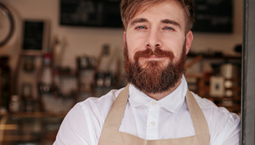 Ginger man with a white shirt and tan apron on
