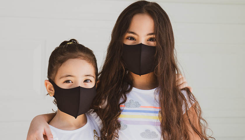 Two young, brunette girls wearing black masks