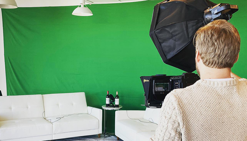 Person setting up lighting in front of green screen filming location