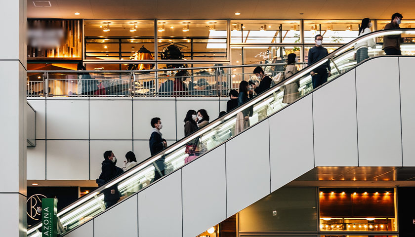 People on an escalator in an indoor shopping mall